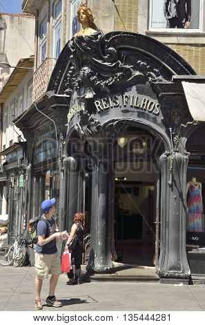 PORTO, PORTUGAL - AUGUST 5, 2016: A man watching a historical clothes shop decorated in the Art-Nouveau style in Saint Catarina street in Porto Portugal