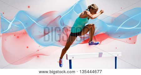 Athlete woman jumping a hurdle against blue wave