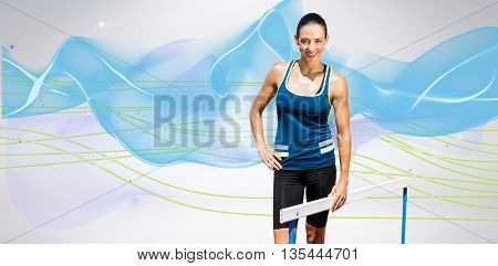 Portrait of sportswoman posing next to hurdle against blue wave