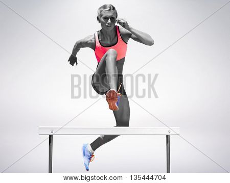 Athletic woman practicing show jumping against grey background