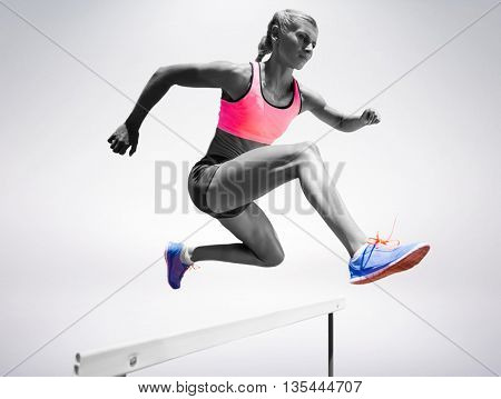 Sporty woman jumping a hurdle against grey background