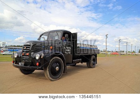 FORSSA, FINLAND - AUGUST 2, 2015: Moving dark green Ford Thames pick up truck year 1952 and old fashioned milk churns on the public event of Pick-Nick Car Show 2015.