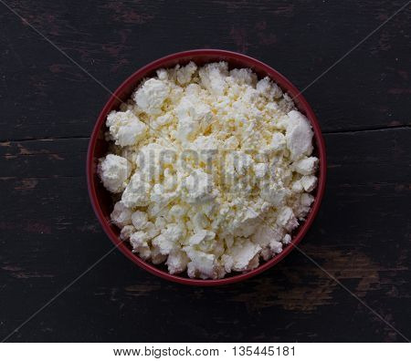 red plate with white milk curds on the old black wooden table. top view close-up