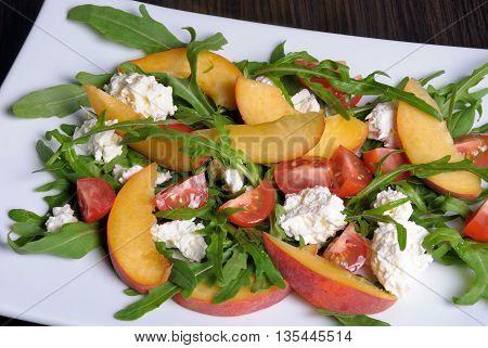 Salad with slices of peach cherry tomatoes arugula feta