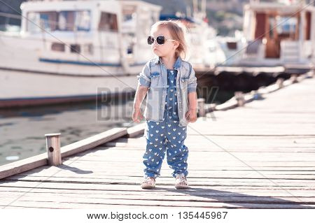 Stylish baby girl wearing denim suit and jacket at wooden pier. Summer season. Child standing outdoors.