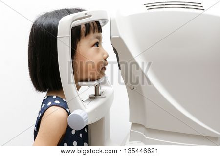 Asian Little Chinese Girl Doing Eyes Examination Through Auto Refraktometer