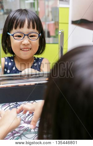 Asian Little Chinese Girl Choosing Glasses