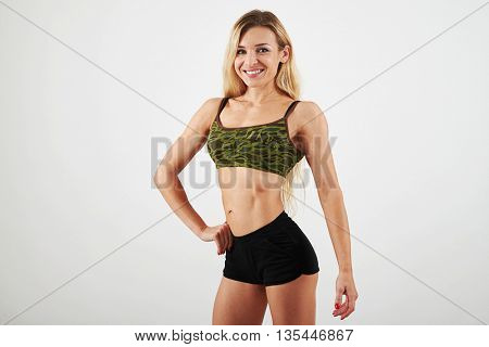 Young sexy muscular woman posing with one hand on hip isolated over white background
