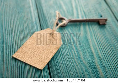 Old Rusty Key With A Paper Label On The Wooden Board