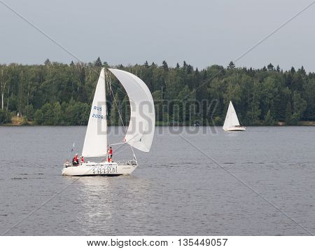 Moscow region - 9 June 2015: Team of people sailing on a small sailing boat and the wind blowing in the white sail summer Pestovo Reservoir June 9 2015 Moscow Region Russia
