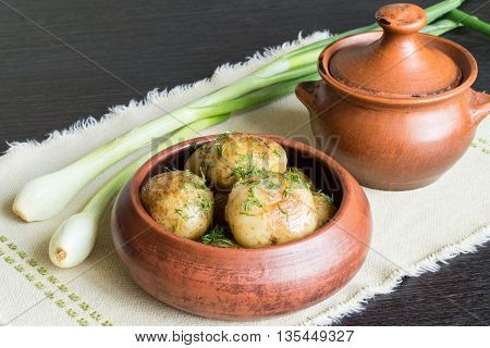 Bowl with boiled potato, an earthenware pot and green onions on a napkin on a dark wooden background.