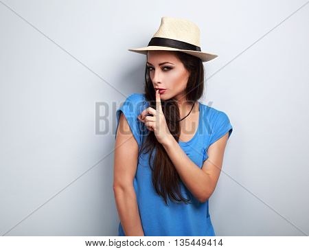 Beautiful Makeup Female Model In Summer Casual Hat Showing Secret Sign On Blue Background With Empty