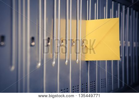 Close up of a yellow envelope sticking out from one of letterboxes in a row.