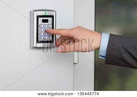 Human hand pressing the security code combination to unlock the door