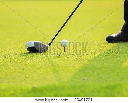 Golf ball behind driver at driving range.