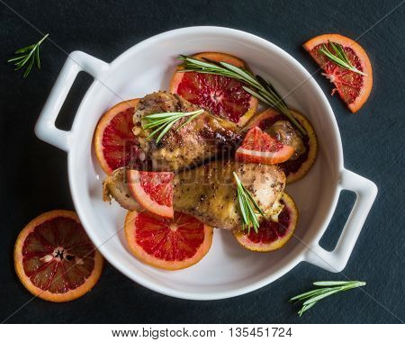 Roasted chicken legs on slices of red oranges in white baking dish. Black slate background. Cooked with the sauce: orange juice mustard olive oil and honey. Top view.