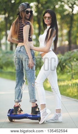 Two Young sexy fit woman in white riding hoverboard - electrical scooter, personal eco transport, gyro scooter, smart balance wheel. Summe photo. Blurred background.