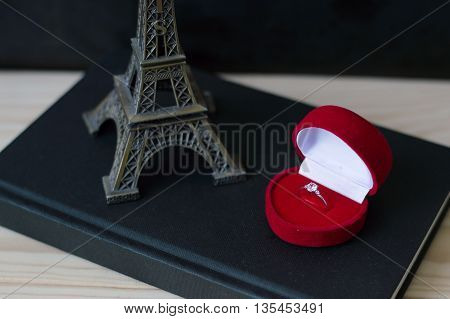 Small metal eiffel tower and an engagement ring in a red box