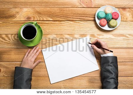 Top view of businesswoman hands writing with pencil in blank sheet of paper