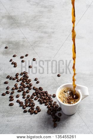 Coffee Poured Into A Cup And Coffee Beans Around