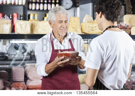 Senior Salesman Holding Cheese While Looking At Colleague