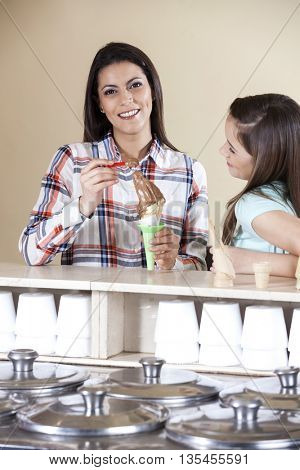 Happy Woman Having Ice Cream With Daughter At Counter