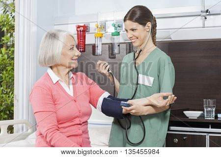 Smiling Nurse Examining Blood Pressure Of Senior Patient