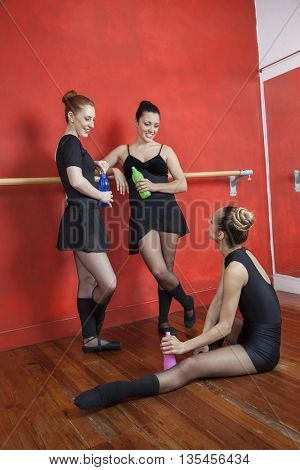 Ballerinas Looking At Friend While Holding Bottles In Studio
