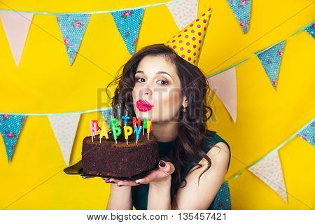 Beautiful caucasian girl blowing candles on her cake. Celebration and party. Having fun. Young pretty woman in green dress and birthday hat is laughing.