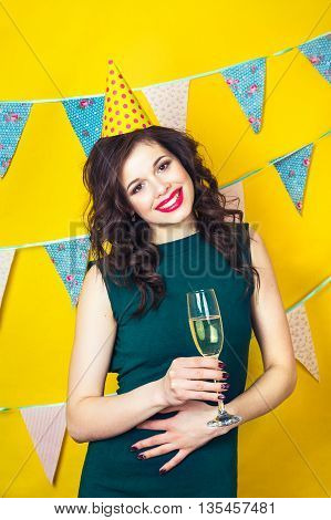 Young celebrating woman green dress, holding a glass of champagne.Celebration and party. Having fun. Young pretty woman in green dress and birthday hat is laughing. Colorful studio portrait with yellow background.