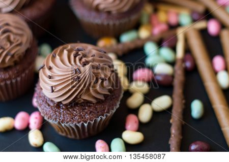 Chocolate cupcake and colorful sweets on black background close up