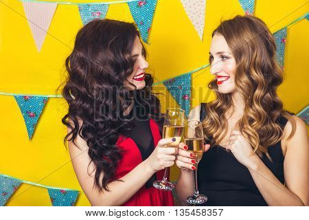 Portrait of joyful friends toasting and looking at camera at birthday party. Attractive friends celebrating a birthday. Smiling girls with glasses of champagne