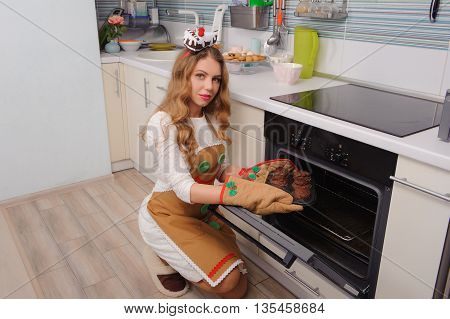 young housewife taking cupcakes from oven and smiling