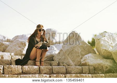 Young hippie woman sitting at the stairs near big stones