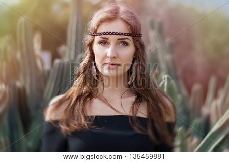 Portrait of a young hippie woman with long hair and blue eyes