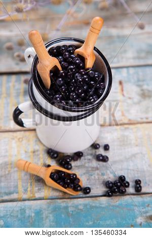 fresh bilberry with wooden shovel in white cups