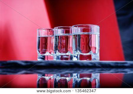 Glasses of vodka on a black stone plate