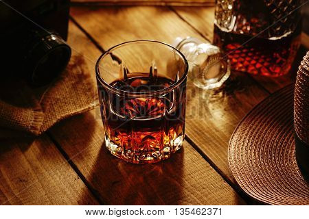 Glass of whiskey and hat on a table