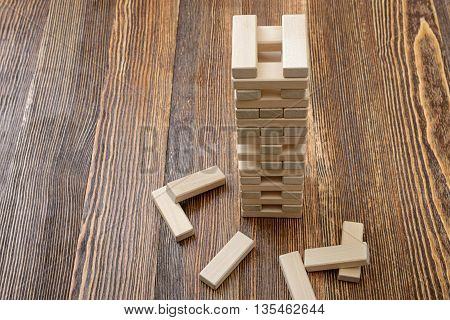 The tower of wooden blocks placed on a table.. Removing blocks from a tower. Keeping balance. Full concentration. Entertainment activity. Game of physical and mental skill. Close-up photo.