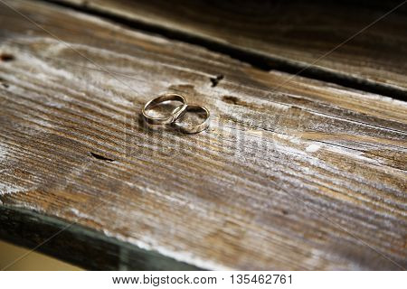 gold wedding rings on wood backgroung texture