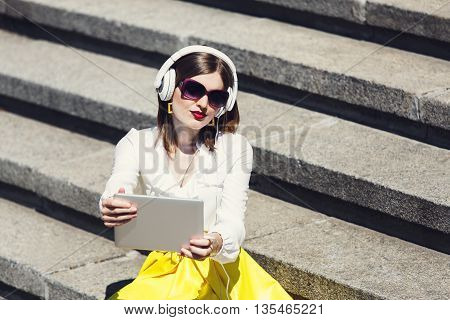 Young woman student listens music from tablet pc outdoors. Girl with earphones wears sunglasses sit at downstairs. Musical leisure. Having fun, relax outdoors.