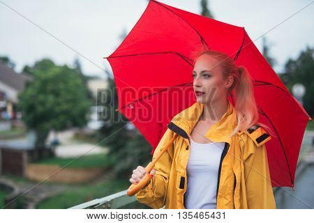 Beautiful woman holding umbrella and walking in the city.