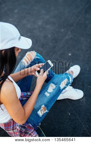 Young skater girl surfing the net outdoors.