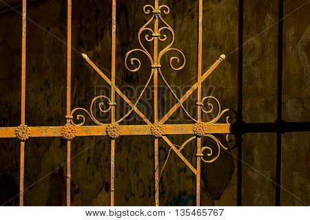 Old metal wrought decorative pattern on iron rusty vintage fence on dark background