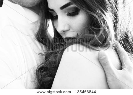 Young newlywed couple of woman in wedding dress and man embracing in field in sunlight outdoor black and white