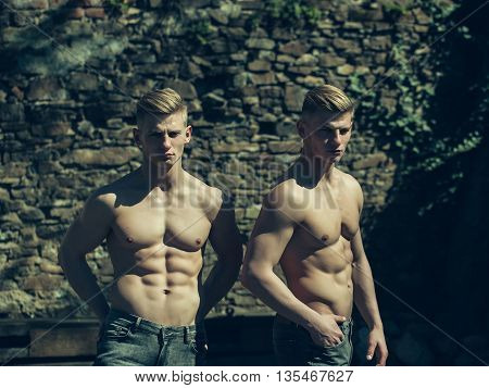 Twin brothers two muscular bodybuilders with bare torso strong young men sexy models in jeans stand hands in pockets on mural background