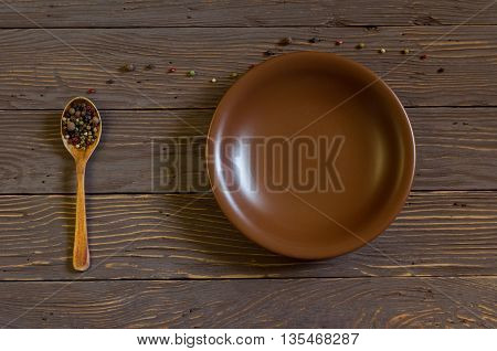 Wooden spoon with colored pepper lies on a rustic wooden table. Near earthenware dish
