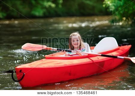Family on kayaks and canoe tour. Little girl paddling in kayak in a river on a sunny day. Children in summer sport camp. Active preschooler kayaking in a lake. Water fun during school vacation.