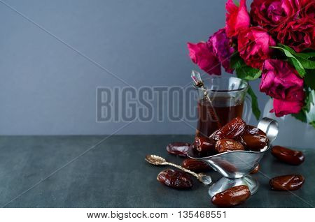 Traditional arabic tea set and dried dates. roses in the background