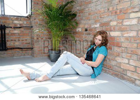 portrait of woman resting near the brick wall